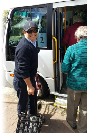 Driver helps clients onto shuttle bus